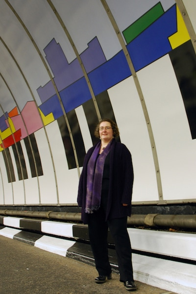 The artist, Ali Barker, next to the Liverpool Composition skyline mural in the Birkenhead Tunnel